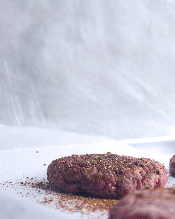 raw beef burger patties covered in dried seasoning