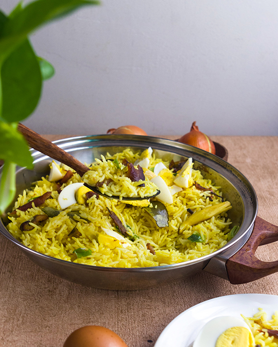 A pan of yellow basmati rice with flaked smoked catfish and chopped hard-boiled eggs