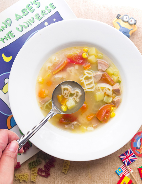 a bowl of chicken soup with animal shape pasta, corn, tomato, carrot, and potato