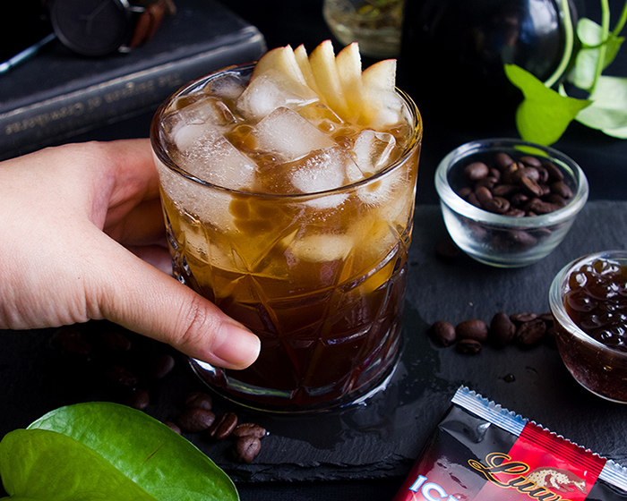 a glass of iced coffee with lots of ice cubes and thinly sliced apples