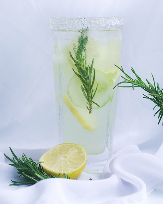 a glass of aloe vera lemonade with fresh rosemary sprigs, lemon and cucumber slices