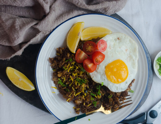 Black aromatic fried rice with sunny side up egg with cherry tomatoes