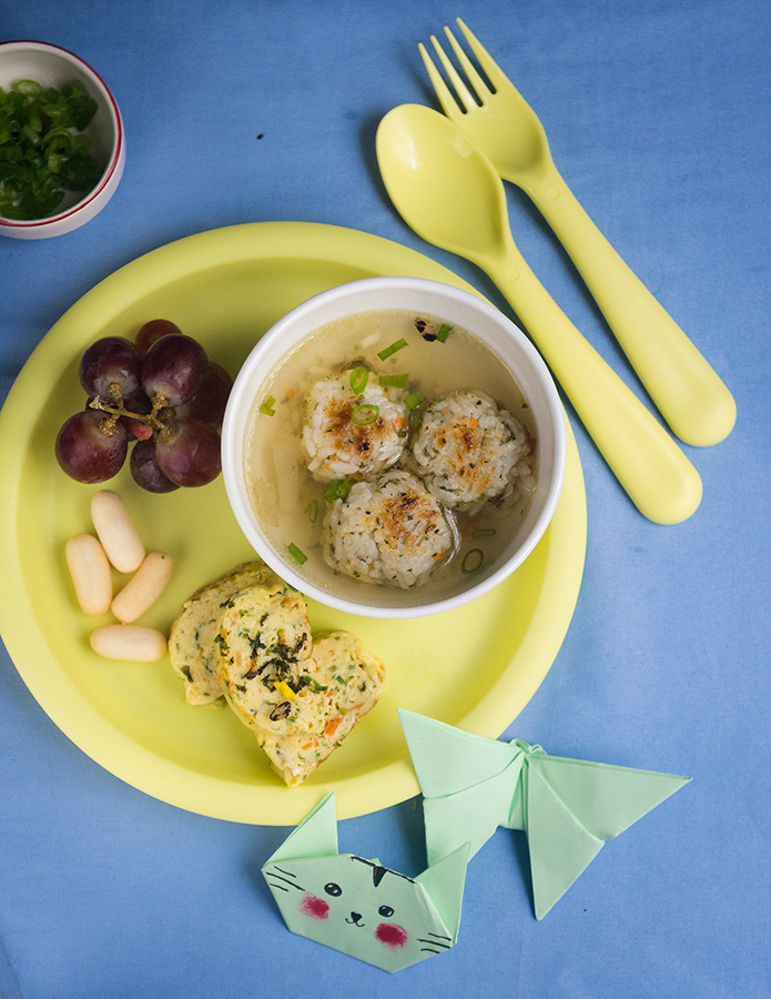 bowl filled with grilled rice balls soup on a yellow plastic plate for kids with egg rolled and grapes on the side