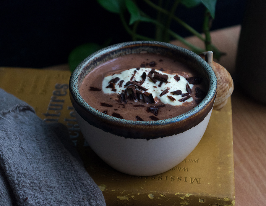 a cup of rich hot chocolate topped with whipped cream and shaved dark chocolate