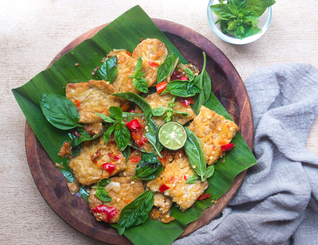 Tempe Penyet in a wooden plate layered with banana leaves